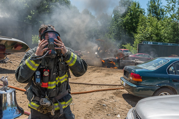 GARDNER - A Gardner firefighter masks up before attacking a car fire at Lajoie's Used Auto Parts, 27 Hill St. Monday July 9, 2018 [Photo/Jim Marabello]