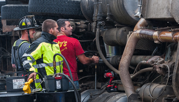 WESTMINSTER - Workers from Ricky's Towing pump diesel fuel out of the saddle tanks of a tractor trailer dump truck that rolled over at the corner of Depot Rd and Village Inn Rd. The driver suffered minor injuries but the truck leaked approximately 20 gallons of diesel fuel and hydraulic fluid. Monday August 13, 2018 [Photo/Jim Marabello]
