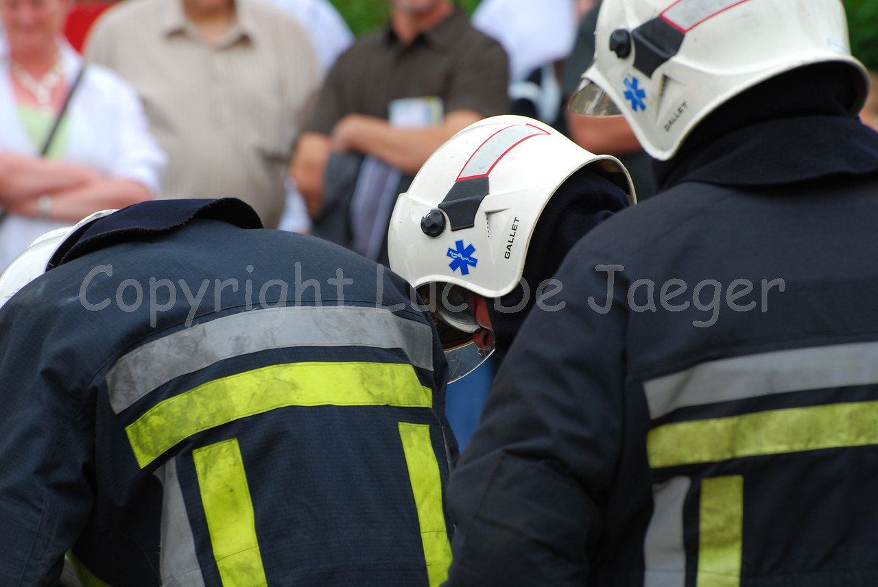 Firefighters trying to rescue someone out of a crashed car. Most firefighters wear the Gallet helmet.