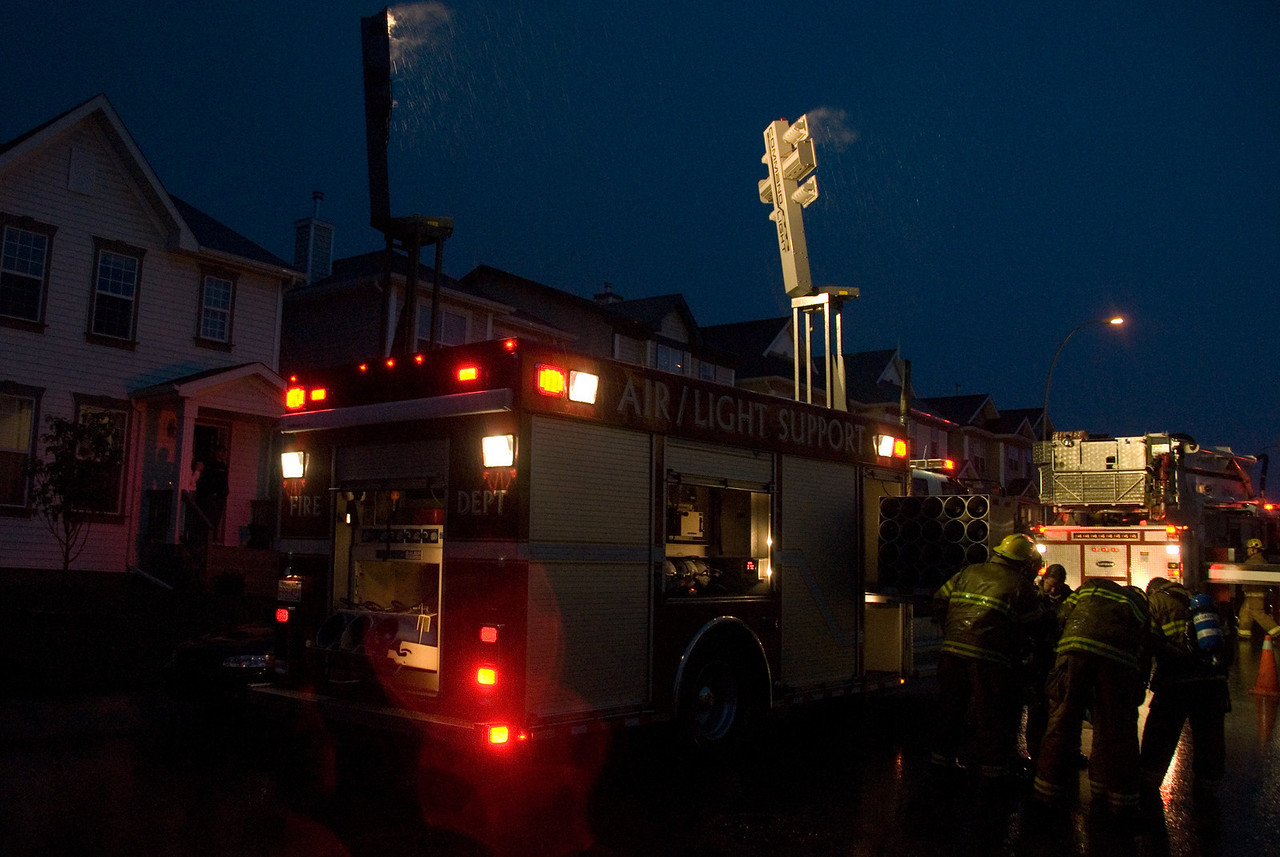 This fire truck with flood lights stayed active until around 11:30 pm, providing light for the fire fighters working on the house.