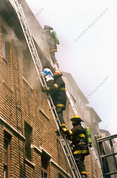 Firefighters from Ladder 9 make a rescue at a fire on North Street.