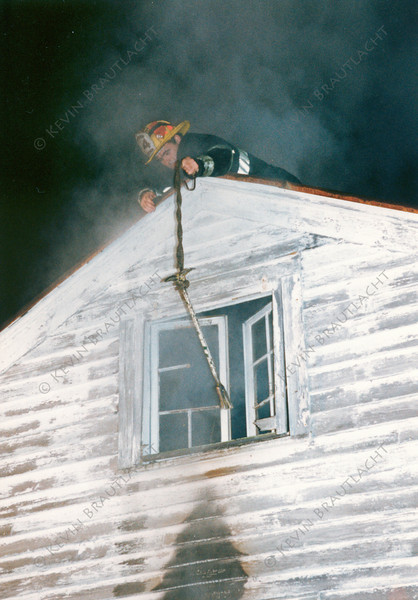 Officer from Ladder 14 demonstrates venting a window using a halligan and hose rope.