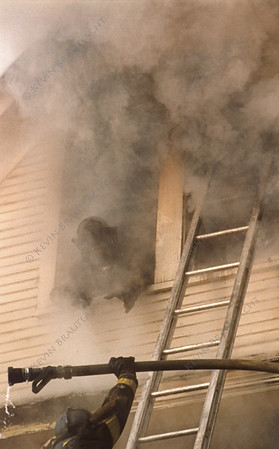 Firefighter reaches for hoseline from the attic window at this west side multiple alarm