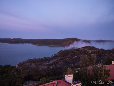 Dawn from Barrenjoey lighthouse shows the fire still burning on the western side of the headland