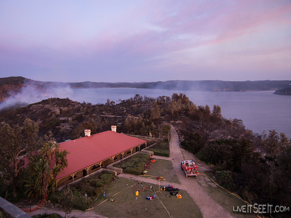 Dawn from Barrenjoey lighthouse shows the fire still burning on the western side of the headland. Foregound shows some of the equipment used to protect the buildings