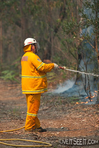 A firefighter cools trees on the edge of the burn.