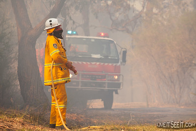 A firefighter stands at the ready with a hose reel while monitoring burning operations