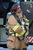 Female firefighter dons PPE during a house fire