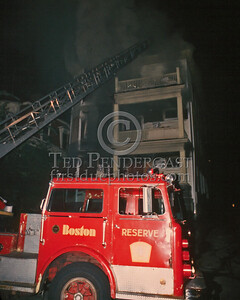 August 22,1986 - Fire involving the rear porches of a 3-Decker on Pleasant St in Dorchester. The fire was held to a Working Fire. Ladder 7, using a well-worn Maxim tiller reserve piece, at the front of the building.