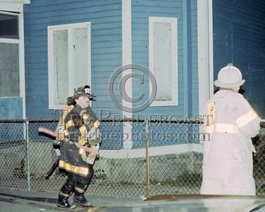 "**RESCUES MADE** June 1986 - All Companies Working at a fire off of Blue Hill Ave (Box#, Street, etc. lost to time) in Mattapan. Report of people trapped. At least one adult occupant jumped from an upper floor window. I heard a FF yell ""Where's H&H, I got one!"" and swung around to snap this photo (bad focus I know). A member of Rescue-2 rescued this unconscious child from the building. I do not know whether the child made it or not but as I recall at least one person died at this fire."