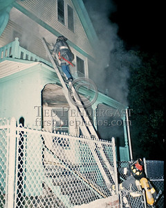 July 1986 - A 'truckie' scales a ground ladder to vent the second floor windows at this 2nd Alarm on Magnolia Square in Dorchester.