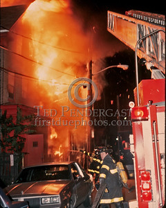 "Sat., Sept. 27,1986 - Fire Alarm reported they were ""Receiving Calls"" for a fire in the alley of a building in Andrew Square at the intersection of Dorchester Avenue & Dexter St (South Boston). Companies had chased several trash fires in the area much of the evening. As misfortune would have it, the two first-due Engines and the first-due Truck (E39, 21 & L18) were all committed to other stills at the time the box was struck. District 6 arrived by himself and found a significant fire in the alley off Dexter St opposite the Andrew Square MBTA Station. He transmitted three alarms as the fire communicated to three buildings while he waited for the first companies to arrive. Five Alarms were transmitted on Box 7234 in total for this fire.  Ladder 4 and Engine 14 on scene and stretching. Another little story here - there was a brief delay between the previous photo and this one as one of the guys riding with me that night (Mike) pulled an occupant out of the open red door you see in the image here. I turned around and saw him disappearing briefly into the doorway and emerging with a male who Mike had heard yelling for help. We grabbed one of Boston's Finest and 'suggested' an ""H&H"" (ambulance) might be in order. Note the progress the fire has made during that time. My guess would be approximately 3-5 minutes between these two photos."