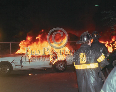 "October 1986 - A ""Cah Fiya"", or rather two cars on fire, in a parking lot off of Melnea Cass Boulevard & Harrison Avenue in Roxbury. Thats either Engine 3 or Engine 14 stretching a line on the fire."