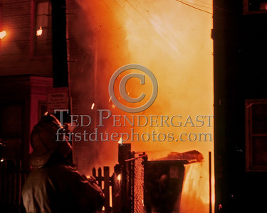 "Sat., Sept. 27,1986 - Fire Alarm reported they were ""Receiving Calls"" for a fire in the alley of a building in Andrew Square at the intersection of Dorchester Avenue & Dexter St (South Boston). Companies had chased several trash fires in the area much of the evening. As misfortune would have it, the two first-due Engines and the first-due Truck (E39, 21 & L18) were all committed to other stills at the time the box was struck. District 6 arrived by himself and found a significant fire in the alley off Dexter St opposite the Andrew Square MBTA Station. He transmitted three alarms as the fire communicated to three buildings while he waited for the first companies to arrive. Five Alarms were transmitted on Box 7234 in total for this fire.  District 6 watching the fire burn into the 3rd floor of the building on the corner. Still no companies. Its worth mentioning here that it was a windy night and all three of the exposed buildings were shingled with asphalt shingles (often referred to at least around here as ""gasoline shingles""). The speed and ferocity with which this fire grew is understandable under these conditions."