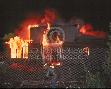 May 24,1986 - 3 Alarms Box 3757 for a large commercial building used to house construction equipment at the end of Glenwood Avenue off Hyde Park Avenue (Hyde Park). Firefighter cuts the fence along the RR right-of-way to gain access to the rear of the building.