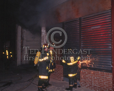 October 1986 - 2 Alarms transmitted for a fire in an autobody shop on Walk Hill St at Blue Hill Avenue (Mattapan).  Using a saw to cut the locks on the rolldown security gates.