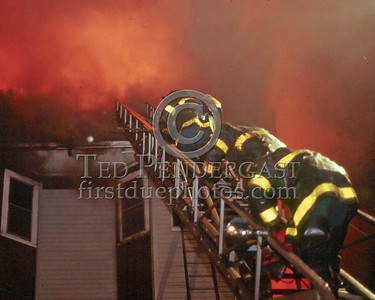May 17,1986 - 2 Alarms Box 3182 for a 3-Decker under renovation on Adams St near Park St in Dorchester. Rear porches of a building under renovation. Here Ladder 7 comes off the roof after ventilating.