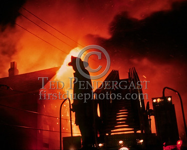 "Sat., Sept. 27,1986 - Fire Alarm reported they were ""Receiving Calls"" for a fire in the alley of a building in Andrew Square at the intersection of Dorchester Avenue & Dexter St (South Boston). Companies had chased several trash fires in the area much of the evening. As misfortune would have it, the two first-due Engines and the first-due Truck (E39, 21 & L18) were all committed to other stills at the time the box was struck. District 6 arrived by himself and found a significant fire in the alley off Dexter St opposite the Andrew Square MBTA Station. He transmitted three alarms as the fire communicated to three buildings while he waited for the first companies to arrive. Five Alarms were transmitted on Box 7234 in total for this fire.  Out of focus but a shot from behind Ladder 4..."