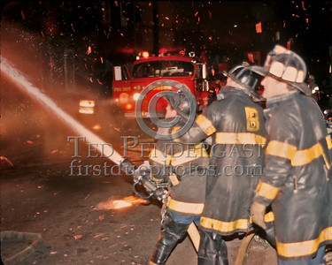 "Sat., Sept. 27,1986 - Fire Alarm reported they were ""Receiving Calls"" for a fire in the alley of a building in Andrew Square at the intersection of Dorchester Avenue & Dexter St (South Boston). Companies had chased several trash fires in the area much of the evening. As misfortune would have it, the two first-due Engines and the first-due Truck (E39, 21 & L18) were all committed to other stills at the time the box was struck. District 6 arrived by himself and found a significant fire in the alley off Dexter St opposite the Andrew Square MBTA Station. He transmitted three alarms as the fire communicated to three buildings while he waited for the first companies to arrive. Five Alarms were transmitted on Box 7234 in total for this fire.  Operating a big line on Dexter St. Focus is off but note the fire storm of embers and burning chunks smashing down into the street. Oh and the spare ALF tiller that Ladder 18 was using... yeah they finally cleared the still and came to play."