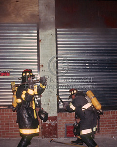 October 1986 - 2 Alarms transmitted for a fire in an autobody shop on Walk Hill St at Blue Hill Avenue (Mattapan).  Opening up! A Truck company uses an adz and sledge to break the locks on these rolldown security doors.