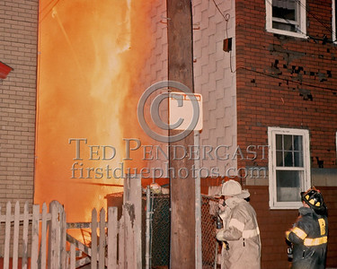 "Sat., Sept. 27,1986 - Fire Alarm reported they were ""Receiving Calls"" for a fire in the alley of a building in Andrew Square at the intersection of Dorchester Avenue & Dexter St (South Boston). Companies had chased several trash fires in the area much of the evening. As misfortune would have it, the two first-due Engines and the first-due Truck (E39, 21 & L18) were all committed to other stills at the time the box was struck. District 6 arrived by himself and found a significant fire in the alley off Dexter St opposite the Andrew Square MBTA Station. He transmitted three alarms as the fire communicated to three buildings while he waited for the first companies to arrive. Five Alarms were transmitted on Box 7234 in total for this fire.  Here the District Chief and his Aide observe conditions in the alley. My guess would be he has transmitted the Working Fire and is radioing a report or orders to the incoming companies..."