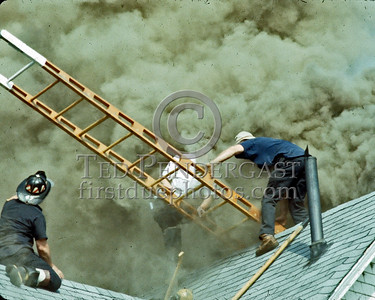 WINCHESTER, Mass. - July 7,1986 - 4 Alarms struck for this fire in a large single-family home on Wedgemere Avenue. The fire started in the basement and spread via the walls to the attic. - The Winchester FFs on the roof reposition a wooden ladder to fascilitate their removal from the roof.