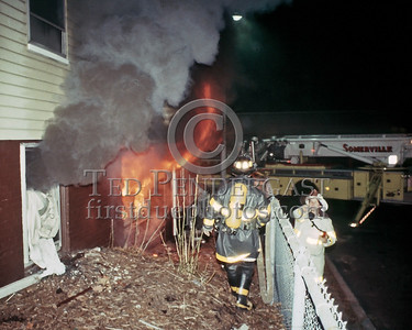 SOMERVILLE, Mass. - Dec.6,1986 - 4 Alarms transmitted for this fire at 202 Highland Avenue. Here Deputy Salvi redirects the Engine company to enter the building via the rear door.