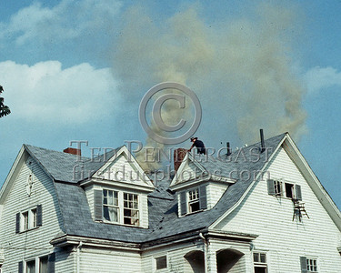 WINCHESTER, Mass. - July 7,1986 - 4 Alarms struck for this fire in a large single-family home on Wedgemere Avenue. The fire started in the basement and spread via the walls to the attic. Here firefighters have vented the roof and the fire beginning to gain headway in the attic space.