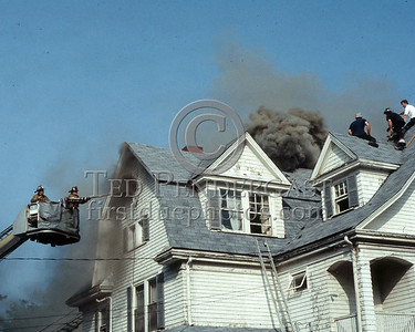 WINCHESTER, Mass. - July 7,1986 - 4 Alarms struck for this fire in a large single-family home on Wedgemere Avenue. The fire started in the basement and spread via the walls to the attic. - Medford firefighters from Tower 1 vent attic windows as Winchester FFs remain on the roof.