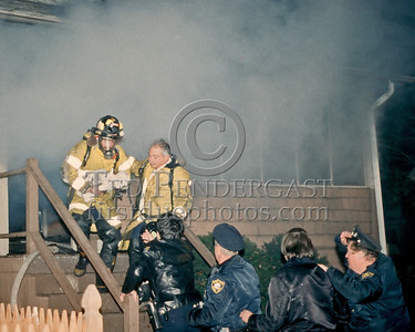QUINCY, Mass. - Nov.15,1986 - A Firefighter emerges having rescued an infant from this burning home on Milton Road. 2 Alarms were transmitted.