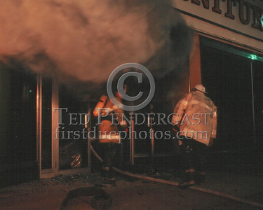 QUINCY, Mass. - May 9,1986 - 5 Alarms in the Furniture City store on Hancock St. Fire on the first floor extended throughout the building over several hours. This photo was taken very early in the fire as the first line advances in to the showroom from the front.