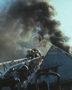 WINCHESTER, Mass. - July 7,1986 - 4 Alarms struck for this fire in a large single-family home on Wedgemere Avenue. The fire started in the basement and spread via the walls to the attic. Here an Arlington firefighter uses Arlington Ladder 2's aerial to make his way off the roof.