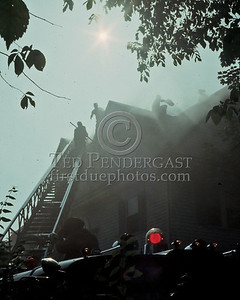 WINCHESTER, Mass. - July 7,1986 - 4 Alarms struck for this fire in a large single-family home on Wedgemere Avenue. The fire started in the basement and spread via the walls to the attic. Here firefighters over Winchester Ladder 1's aerial are opening up the roof. It was a particularly hot and humid July afternoon.