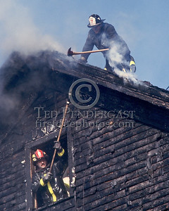 SOMERVILLE, Mass. - December 1986 - 3 Alarms struck for a fire in a house under renovation on Linden Avenue. The Lieutenant of Engine 7 opens up above while a Firefighter from Ladder 2 uses a hook from below.