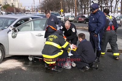 Revere, MA - Firefighters and paramedics extricate a woman from her car after it was struck by a plow truck, 1-8-10.