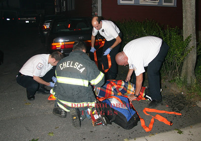 Everett, MA - Fire and EMS personnel treat a patient that was injured when his car crashed into the front of a house. 8-23-08.