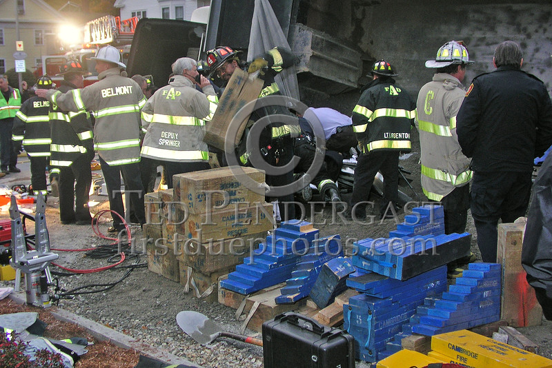 Arlington and Cambridge firefighters assist with the cribbing operation in preparation for lifting the truck and completing the extrication of the patient.