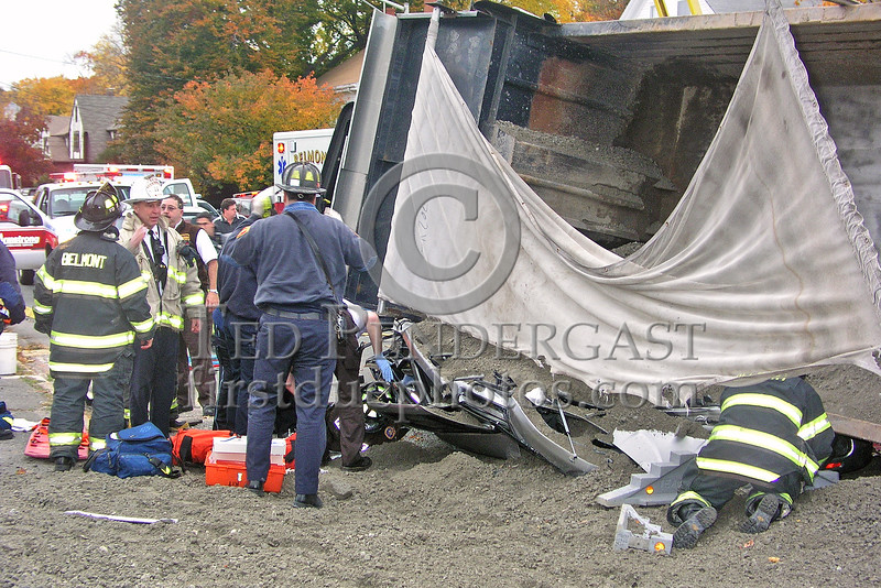 Capt. John Mooney speaks with company officers. Crews work to stabilize the dump truck.
