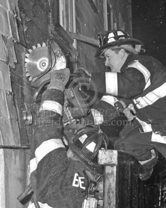 Ladder Co.1 using a saw to open up an exterior wall