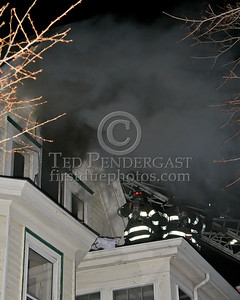 Heavy smoke issuing from the vented windows as engine companies push into the attic from the interior