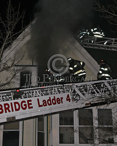 Cambridge Ladder 4's crew vents the front attic windows as Ladder 1 heads to the roof.