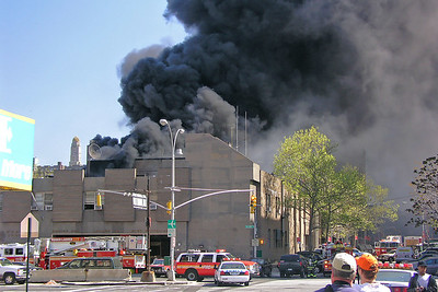 Heavy Smoke Issuing From The Roof Area After The Fourth Of Four Explosions That Helped Spread The Burning Tar Across The Roof Surface - View Is Looking At The Front Of The Firehouse On Tillary St And Down Gold St Towards NYPD's 84th Pct.