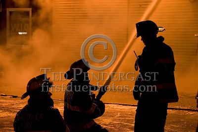 Andover Firefighters With A Big Line On The Springfield St Side Of The Fire While A Lawrence Firefighter Looks On -- 5+Alarms transmitted for a major fire that destroyed or damaged nearly a dozen buildings in South Lawrence in the frigid early morning hours of Mon.,Jan.21,2008.