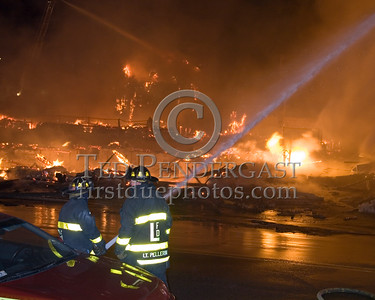 Lawrence Firefighters Operating A Line On Parker St near Market St Infront Of The Remains Of The Building Of Origin -- 5+Alarms transmitted for a major fire that destroyed or damaged nearly a dozen buildings in South Lawrence in the frigid early morning hours of Mon.,Jan.21,2008.