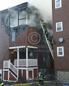 Boston Engine 32's crew operating off a ground ladder in the alley between the fire building & the Bravo exposure.