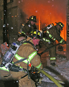 Companies work on withdrawing an interior attack line as fire begins to take possession of the first floor