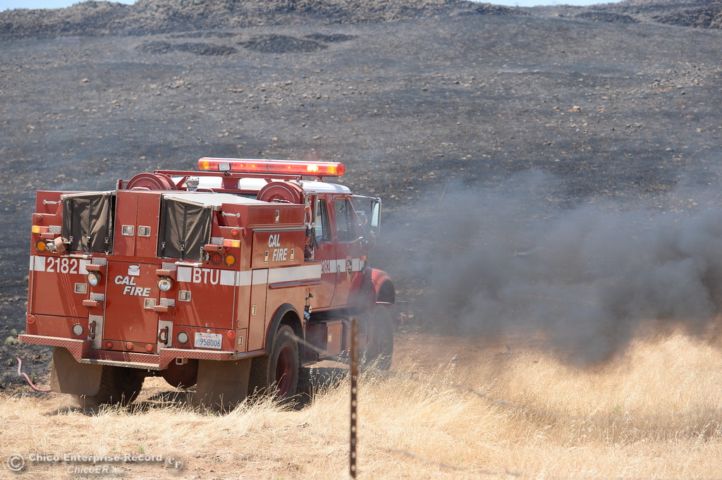 . A puff of black smoke comes from an engine as Firefighters work on a grass fire seen along Nelson Road in Oroville, Calif. Tues. June 6, 2017. (Bill Husa -- Enterprise-Record)