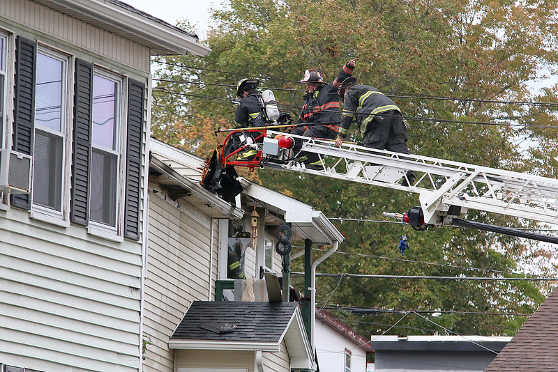 Fire fighters check out the roof of the home at 8 Eden Glen Street after it was secured by police after a standoff and blaze in Leominster on Monday, Oct. 16, 2017. SENTINEL & ENTERPRISE / JOHN LOVE