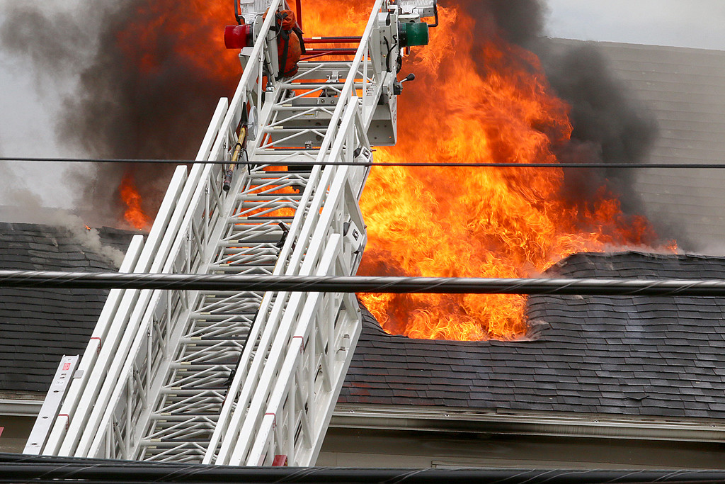 . Fire is seen coming from the roof during a standoff and blaze at 8 Eden Glen Street in Leominster on Monday, Oct. 16, 2017. SENTINEL & ENTERPRISE / JOHN LOVE