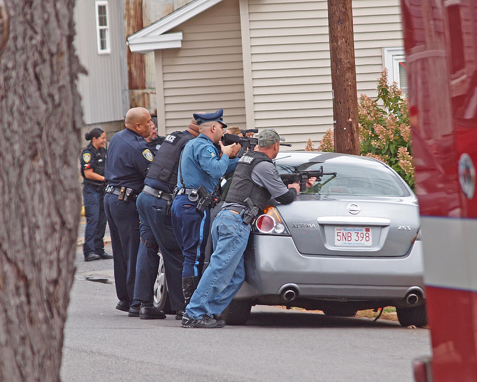 . Police with weapons drawn outside the scene of a fire at 8 Eden Glen St. in Leominster, where a man barricaded himself after police served him court papers early Monday afternoon, according to reports. SENTINEL & ENTERPRISE / ROBERT ALLEN